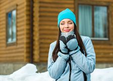 Portrait of woman drinking hot tea. And wearing warm clothes outdoors when going in for winter sports Royalty Free Stock Photos