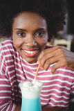 Portrait of woman drinking milkshake with a straw Royalty Free Stock Photo
