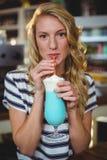Portrait of woman drinking milkshake with a straw Stock Photos
