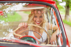 Portrait of woman driving a red vintage car Stock Images