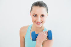 Portrait of woman with dumbbell against wall royalty free stock photography