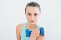 Portrait of woman with dumbbell against wall royalty free stock images