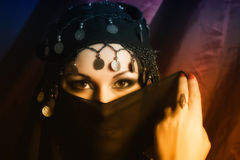 Portrait of a woman in east style. Middle eastern culture: belly dancer with traditional veil Royalty Free Stock Photos