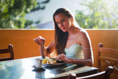 Portrait of woman eating at table