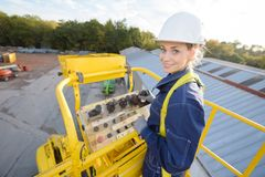 Portrait woman elevated in cherry picker bucket. Portrait of woman elevated in cherry picker bucket stock images