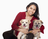 Portrait of woman embracing her dogs, studio shot Royalty Free Stock Images
