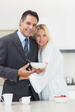 Portrait of a woman embracing well dressed man in kitchen Stock Image
