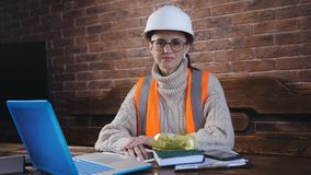 Portrait of a woman engineer in the workplace. Woman engineer in helmet and protective vest sits ha work Desk.