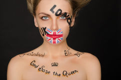 Portrait of woman with english symbols on her face Royalty Free Stock Photo