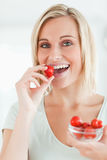 Portrait of a woman enjoying eating strawberries Royalty Free Stock Images