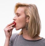 Portrait of a woman enjoying eating strawberries Royalty Free Stock Photography