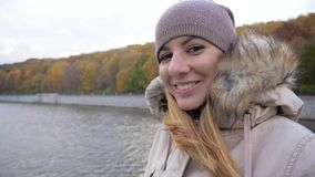 Portrait Woman Enjoys Floating On Tour Boat On River In City At Colorful Autumn. Close-up portrait of smiling happy caucasian woman in warm jacket with fur and stock video