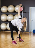 Portrait Of Woman Exercising While Lifting Kettlebell At Gym Royalty Free Stock Image
