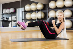 Portrait Of Woman Exercising With Medicine Ball In Gym Stock Image