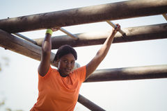 Portrait of woman exercising on monkey bar during obstacle course Stock Photo