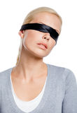 Woman with eyes covered with black ribbon Royalty Free Stock Images