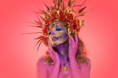 Portrait of a woman with face art in the style of the day of the dead and the Renaissance. Pink background royalty free stock image