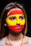 Portrait of woman face supporter fan of Spain national team with painted flag face isolated on black background. Fans emotions. stock photo