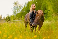 Portrait of woman feeding her arabian horse with snacks in the field stock photos