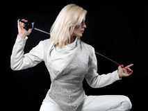 Portrait of woman fencer. Portrait of beautiful blonde woman fencer holding rapier. Olympic sports, martial arts, protection and professional training concept Stock Image