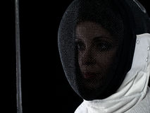 Portrait of woman fencer. Holding rapier. Olympic sports, martial arts, attack and professional training concept Royalty Free Stock Images