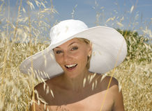 Portrait of woman in field wearing white hat Royalty Free Stock Image