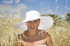 Portrait of woman in field wearing white hat Royalty Free Stock Photos