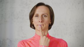 Portrait of woman with finger on her chin under the lips meaning T-letter. Woman touch lips by finger. Sign language for people with disabilities. Portrait of stock video