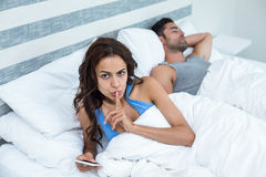 Portrait of woman with finger on lips besides husband sleeping on bed Stock Photography