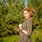 Portrait of woman in fir-tree wood with flowers spring Royalty Free Stock Photography