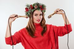 Portrait of a woman with a fir wreath with cones on her head, holds in her hand a nozzle for a cosmetic procedure stock photography