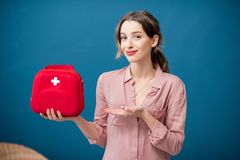 Woman with first aid kit. Portrait of a woman with first aid kit on the blue wall background royalty free stock photo