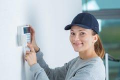 Portrait woman fitting electronic keypad Stock Image