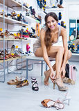 Portrait of woman fitting picked summer footwear Royalty Free Stock Photos