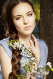 Portrait of woman with flower. Portrait of a beautiful young woman with braid hairdo and flower in her hand Stock Photo
