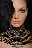 Portrait of woman with flower and black body art Royalty Free Stock Photos