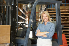 Portrait Of Woman With Fork Lift Truck In Warehouse Stock Photography