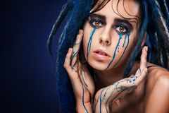 Portrait of a woman freak with dreadlocks. Creative makeup and bright style. Crying girl. Bodyart model girl portrait with colorful paint make up. Sexy woman Stock Photos