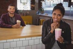 Portrait of woman with friend enjoying milkshake in cafe Stock Image