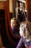Portrait of a little girl in front of a mirror. Reflection of a cute little girl in the mirror Royalty Free Stock Photos