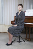 Portrait Of Woman In Front Of Piano. Full length portrait of a serious young woman sitting in front of piano Stock Image