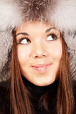 Portrait of a woman in fur hat. Smiling young woman in fur hat over dark background Stock Photos