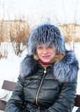 Portrait of a woman in a fur hat. Winter in the city park Royalty Free Stock Photo