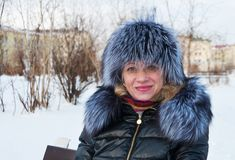 Portrait of a woman in a fur hat. Winter in the city park Stock Photography