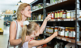 Portrait of  woman and girl buying conserve tomato sauce. Portrait of  positive women and cheerful glad girl buying conserve tomato sauce in glass jar in grocery Stock Images