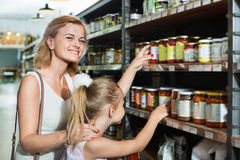 Portrait of  woman and girl buying conserve tomato sauce. Portrait of smiling positive women and glad girl buying conserve tomato sauce in glass jar in grocery Stock Images