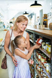 Portrait of  woman and girl buying conserve tomato sauce. Portrait of smiling positive women and girl buying conserve tomato sauce in glass jar in grocery shop Stock Photo