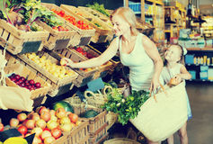 Portrait of  woman and girl buying fresh fruits Stock Image