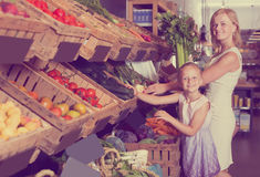 Portrait of woman and girl buying greens Stock Photo