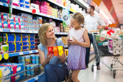 Portrait of  woman and girl holding package with yogurt in groce Stock Images